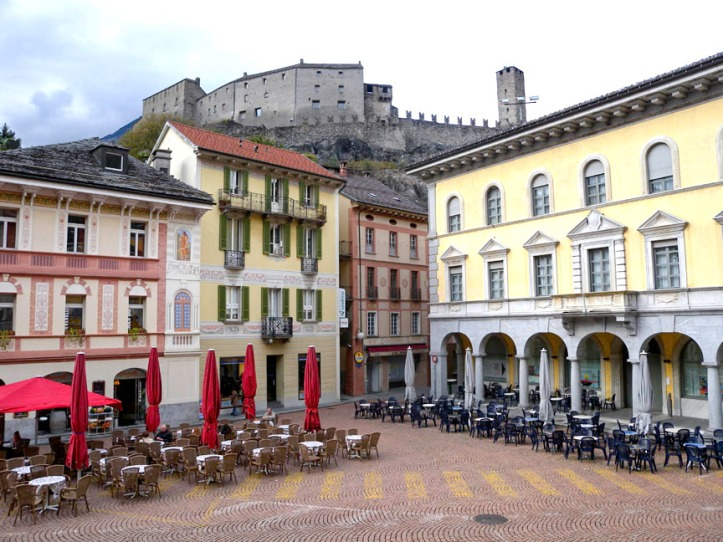 Piazza Collegiata, Bellinzona, from the steps of the Collegiata, with the Castel Grande in the background Photograph by David Hill taken 1 November 2012, about 2.00 pm. Ruskin's balcony can be seen (left) on the house just left of centre. The square was quiet being All Saints Day, but the following day was thronged with people.
