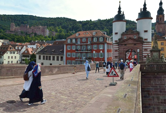 Heidelberg Castle and Heiliggeistkirche from the Old Bridge Photograph by David Hill taken 27 August 2015, 11.46 GMT Turner's sketch is not quite so straightforward as it at first appears. The main part of it is taken from the viewpoint of the photograph. But the castle has been 'brought in' close to the bridge towers, by sketching it from the bay at the base of the statue of Price Elector Carl Theodor.