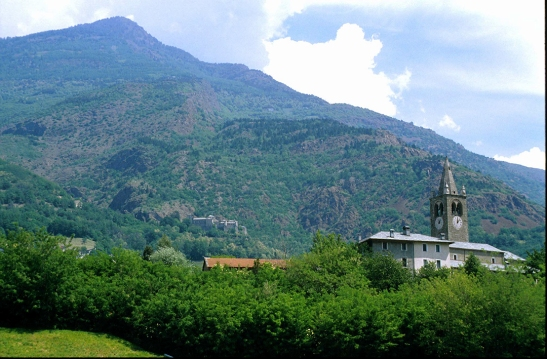 L'Eglise in the Val d'Aosta, with Quart castle beyond Photograph by David Hill taken June 1999.