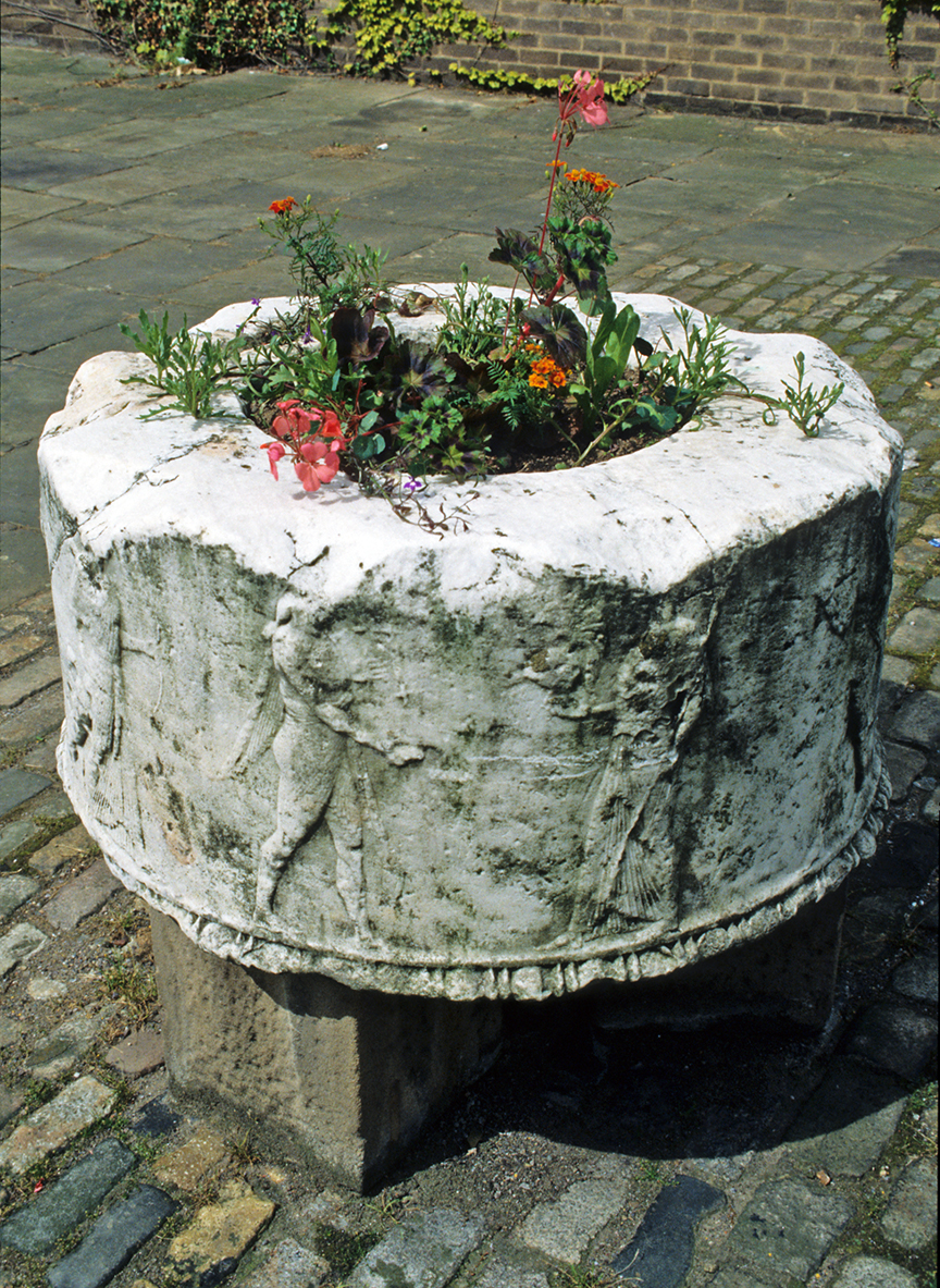 The Corinth Puteal at Bretton Hall Summer service as a plant pot. Photograph by David Hill, taken summer 1993.
